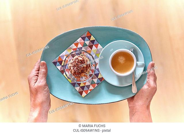 Overhead view of female hands holding plate of dessert and cup of espresso