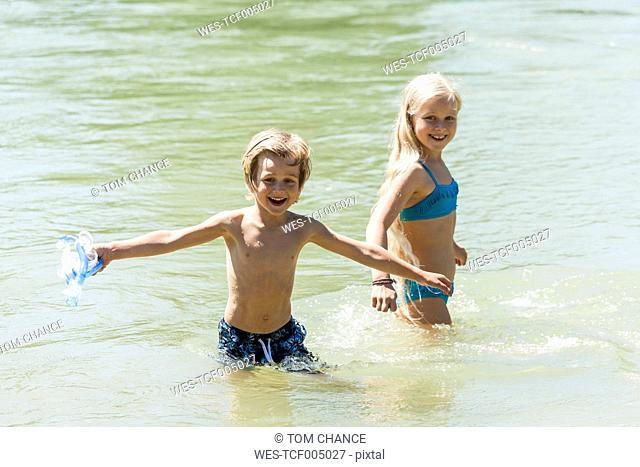 Little boy and his sister bathing in a river