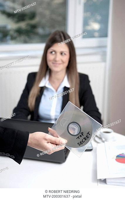 Hand holding CD, young business woman sitting in the background