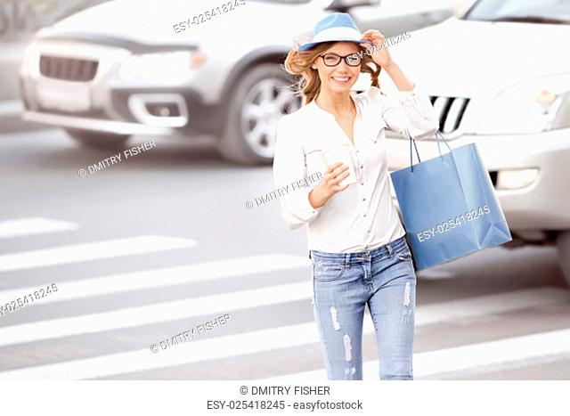 Happy young female student crossing the street with a coffee-to-go cup and tipping hat against urban city background