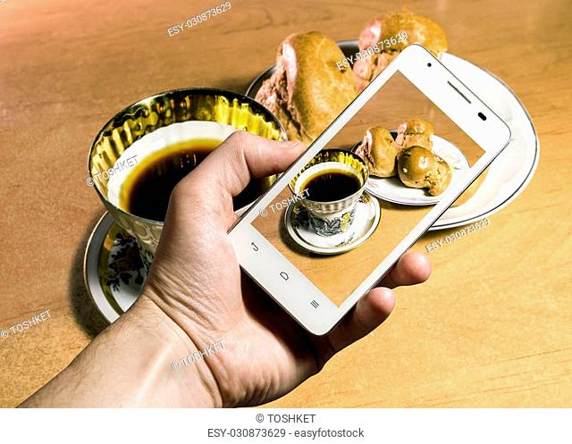 Look for a Cup of coffee and cake through the camera of a smartphone in hand