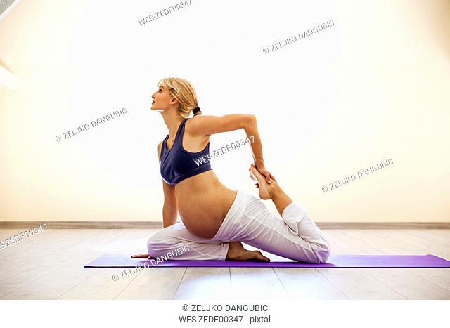 Prenatal yoga, woman doing one-legged king pidgeon pose