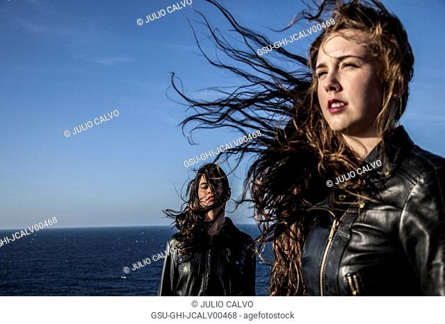 Two Young Women with Hair Blowing in Wind by Sea