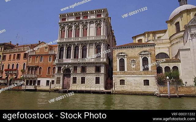 Tracking moving shot along the Grand Canal near Chisea San Germa showing Venetian Palaces, Venice, Italy