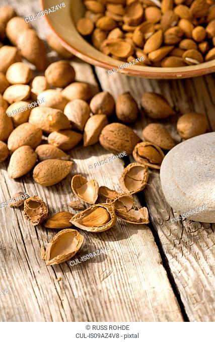 Bowl of almonds (Prunus dulcis) broken and in nutshells on table