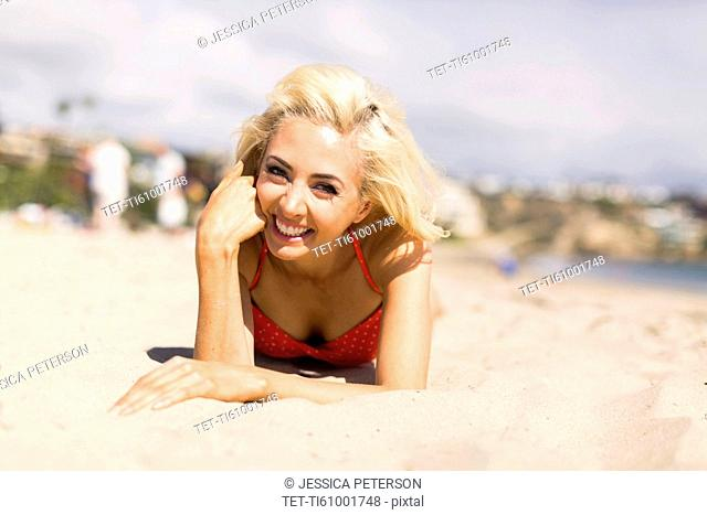 Portrait of blond woman lying on beach