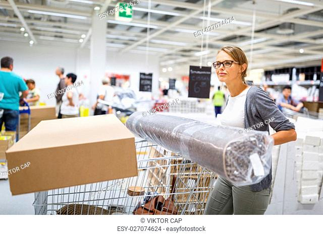Pretty, young woman choosing the right furniture for her apartment in a modern home furnishings store - with a trolley, done shopping, leaving the store