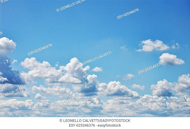Blue sky with fluffy white clouds. Wide format. Photographic Image