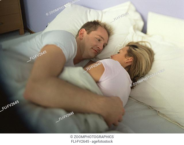 Man and woman embrace in bed