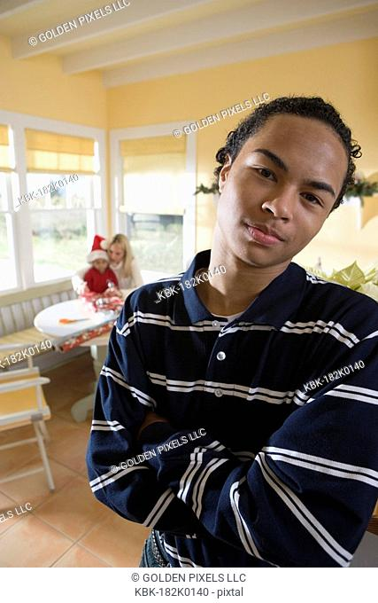 Portrait of a teenager boy with arms folded, family wrapping gifts in background