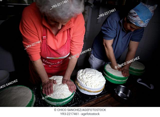 Woman work making Pecorino cheese in Quesos Oliva artisanal cheese making workshop in Villaluenga del Rosario, Sierra de Grazalema Natural Park, Cadiz province
