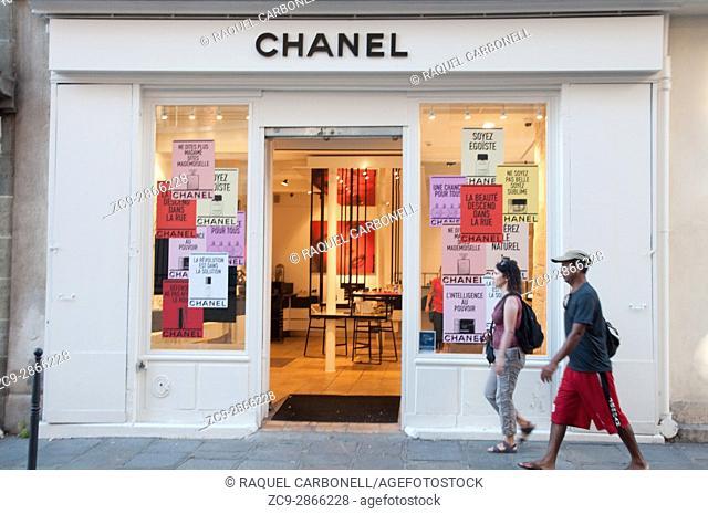 Couple walking down a street passing by Chanel shop. Le Marais, Paris, Ile de France, France