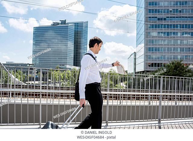 Businessman with rolling suitcase on a bridge checking the time