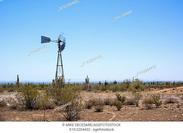 An old windmill in a desert landscape still works