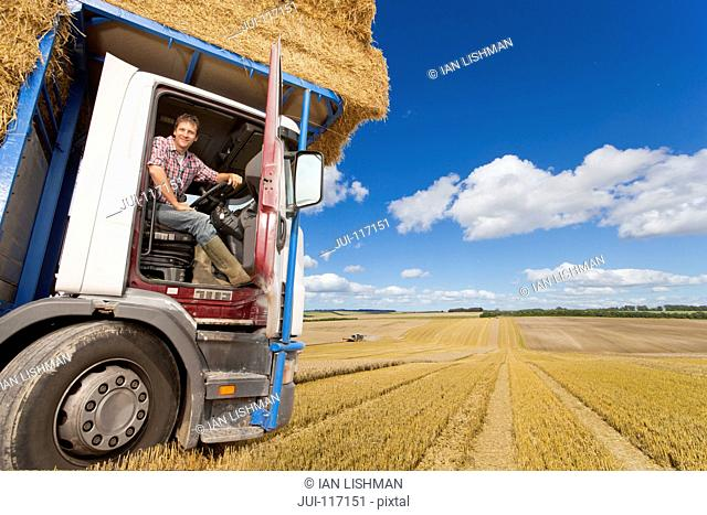 Portrait Of Farmer In Cab Of Lorry Transporting Straw Bales