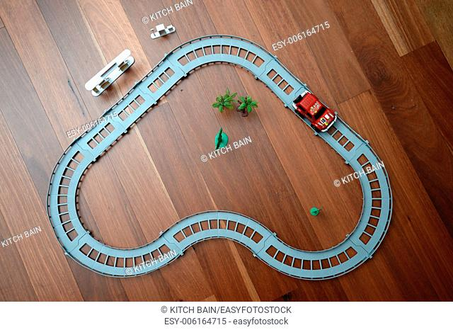 A toy race track on a wooden floor