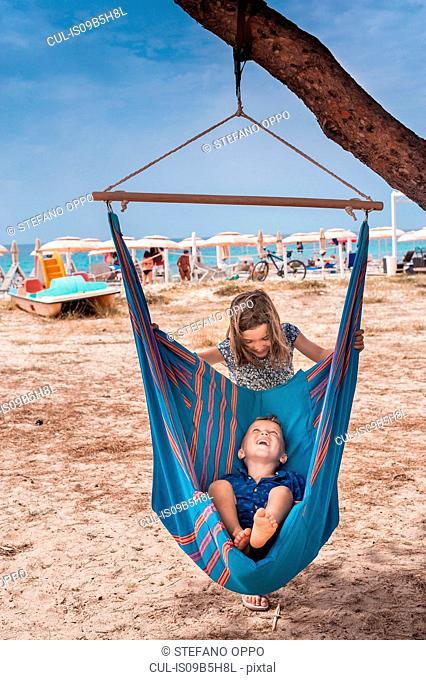 Girl pushing brother in hammock on Poetto beach, Cagliari, Italy