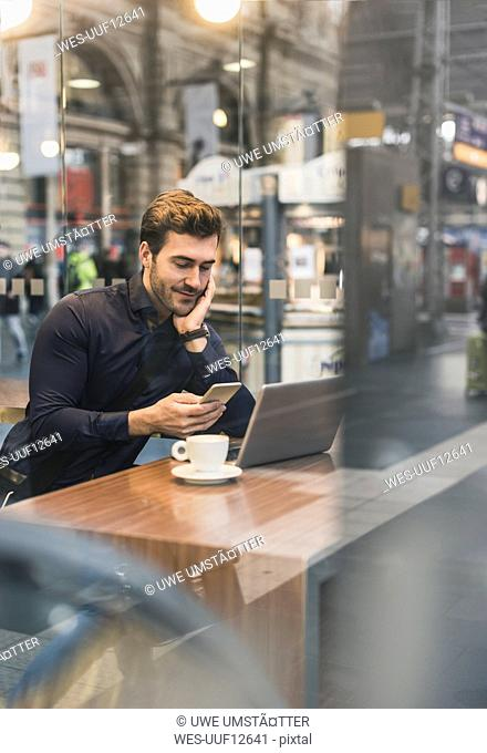 Young businessman in a cafe at train station with cell phone and laptop