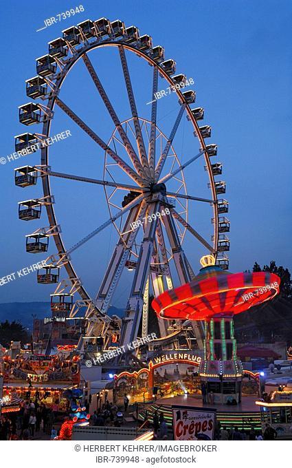 Ferris wheel and swing carousel at a fair in Stuttgart, Baden-Wuerttemberg, Germany, Europe