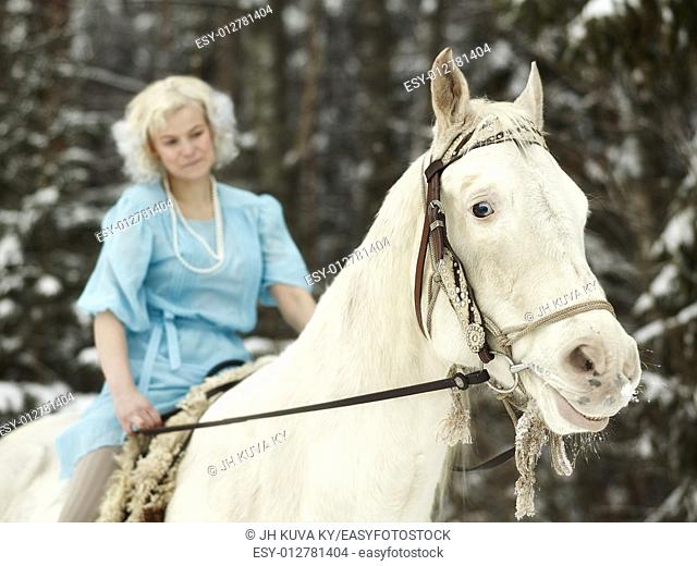 Attractive woman wearing blue dress and she riding a white horse, focus on horse eyes. South Finland in February