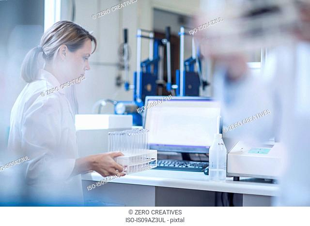 Woman in laboratory, holding rack of test tubes