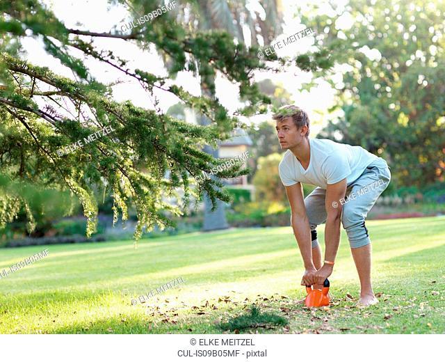 Young man exercising outdoors, lifting weight