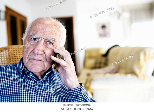 Portrait of senior man telephoning with smartphone at home