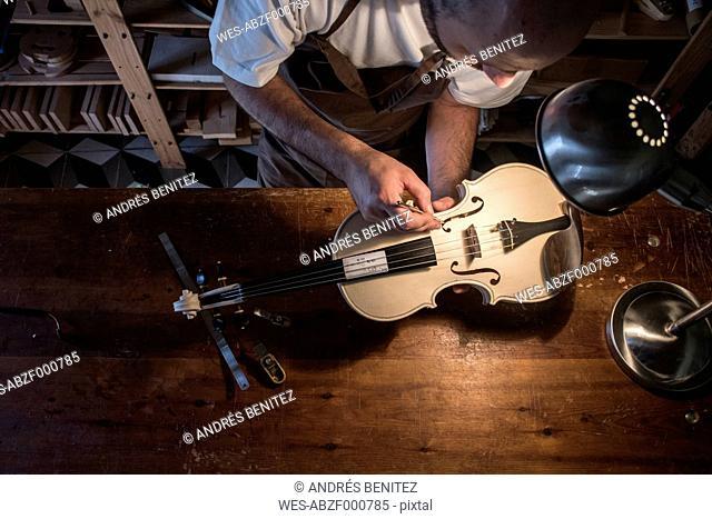 Luthier adjusting the sound post of an unvarnished violin in his workshop