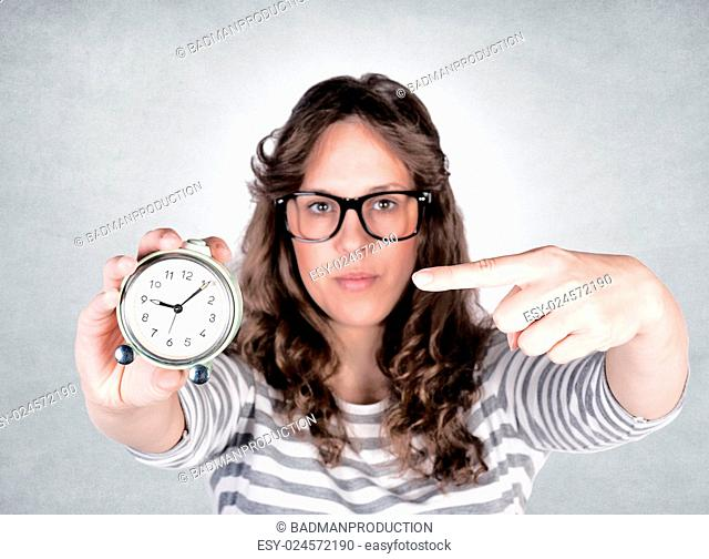 Female pointing her finger on the clock. Selective focus on hand and clock