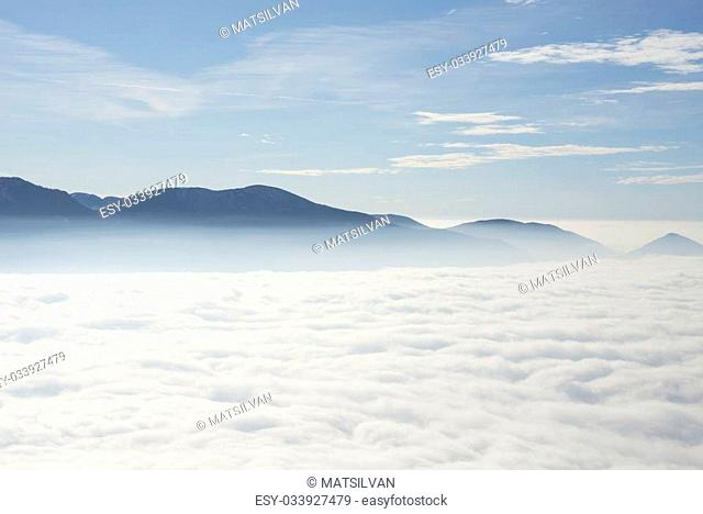 Sea of fog over an alpine lake with mountain