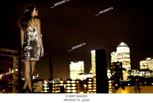 A young woman in a sequined party dress standing on a rooftop at night looking at the city lights