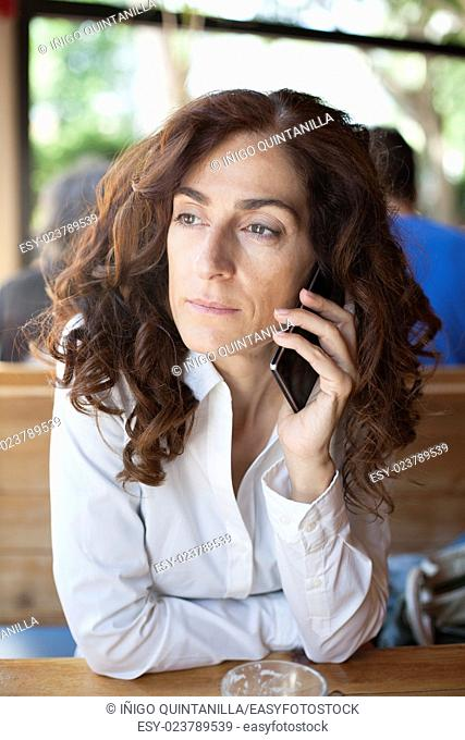 portrait of woman with white shirt curly brunette hair with listen to mobile phone in ear sitting inside light brown wooden cafe