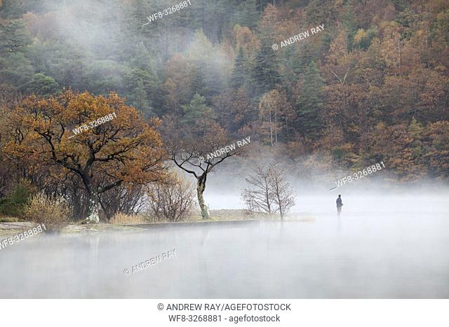 A fisherman near the north end of Crummock Water in the Lake District National Park, captured using a telephoto lens on a still misty morning in late October