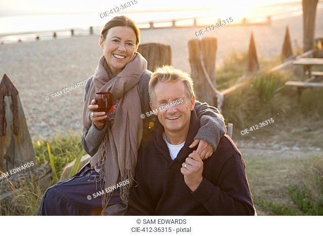 Portrait smiling mature couple holding hands and drinking wine on sunset beach