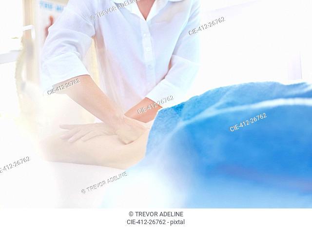 Masseuse rubbing woman's leg
