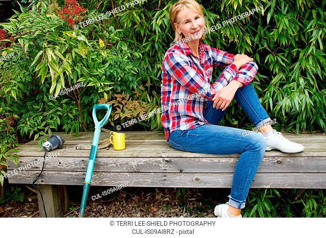 Portrait of mature woman taking a break on garden seat