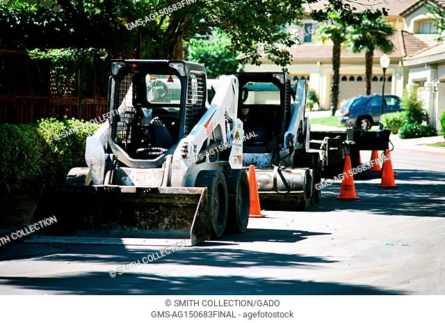A line of front end loader construction vehicles is parked beside a road, with orange traffic cones, during a road construction and resurfacing project in the...