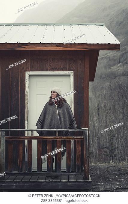 An attractive Woman with stands in front of her cabin and lets her eyes wander across the cold surroundings. Yukon Territory, Canada