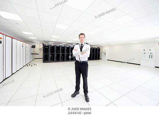 Security guard standing with arms crossed in server room