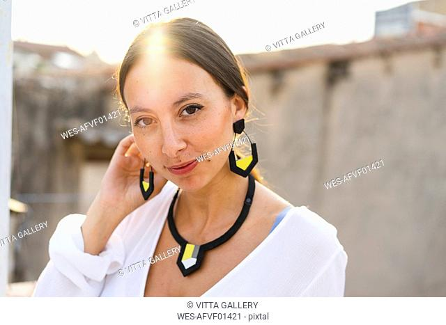 Portrait of young woman wearing modern necklace and earrings