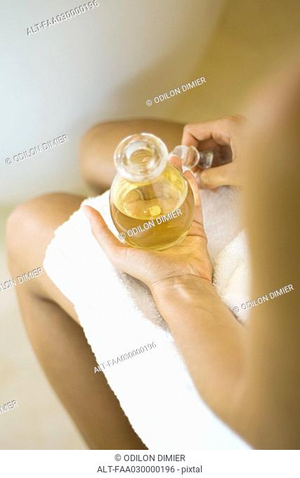 Woman wrapped in towel, holding jar of massage oil, cropped