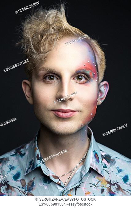 Portrait of beautiful young man with modern hairstyle, artistic multicolor makeup and rhinestones on the face. Studio shot. Black background