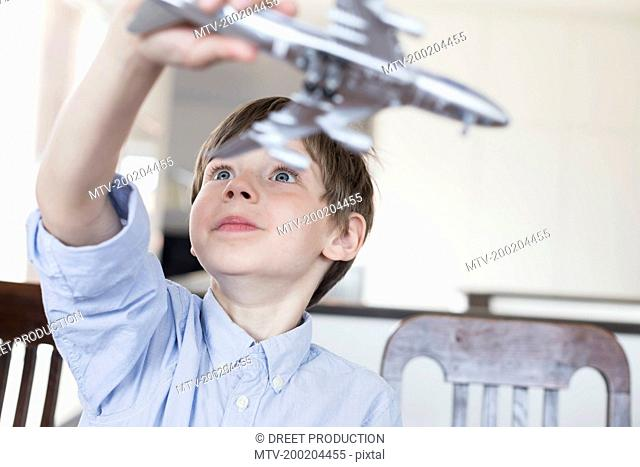 Boy playing with toy aeroplane, smiling