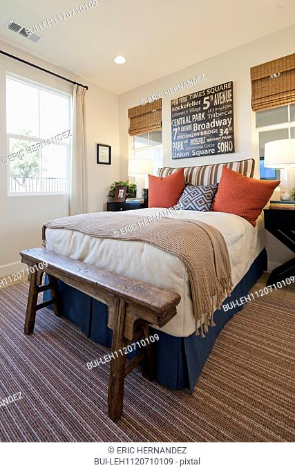 Arranged pillows on tidy bed on carpet floor in the bedroom at home; San Marcos; California; USA