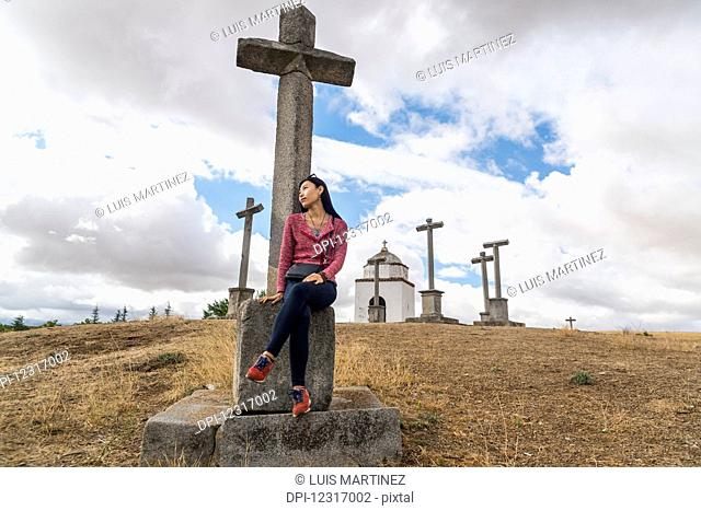 A Chinese young woman sitting on a cross in the surroundings of Segovia; Segovia, Castilla Leon, Spain