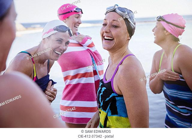 Laughing female open water swimmers drying off with towels