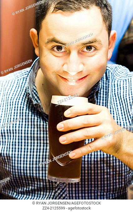 Funny lifestyle photograph of a happy European English man holding and drinking pint of beer with foam head at bar location. Ale drinker