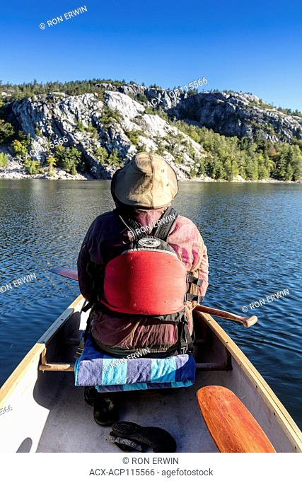 Woman wearing a bug jacket in the front of a canoe in Killarney Provincial Park, Ontario, Canada