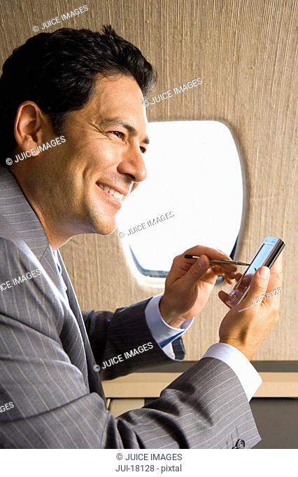 Businessman using electronic organiser on aeroplane, smiling, close-up