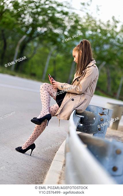 Teenager girl is texting sms message on smartphone